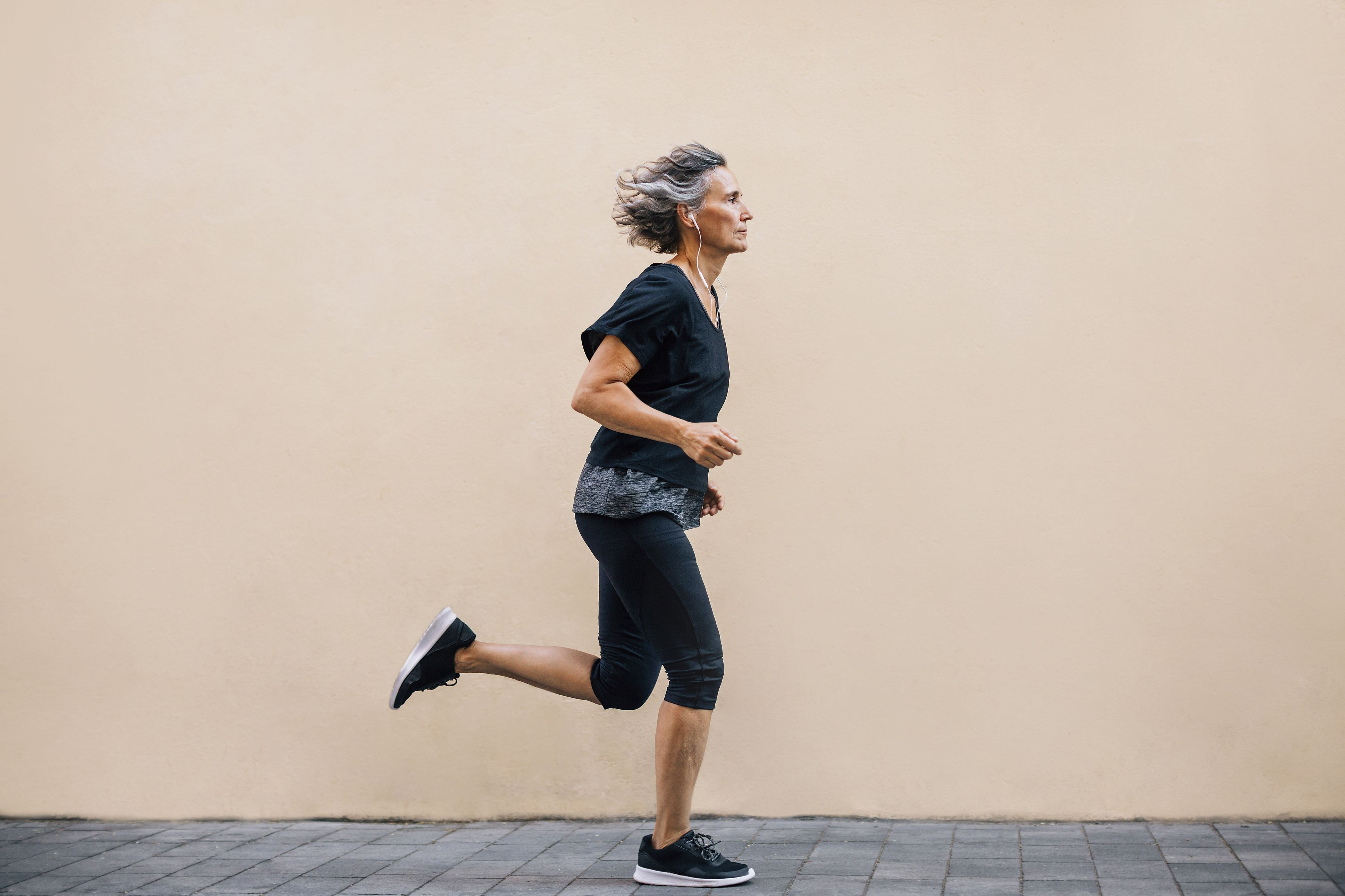 Side view of woman jogging on footpath against wall
