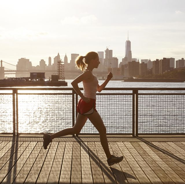 Side view of woman jogging on pier, Manhattan, New York, USA