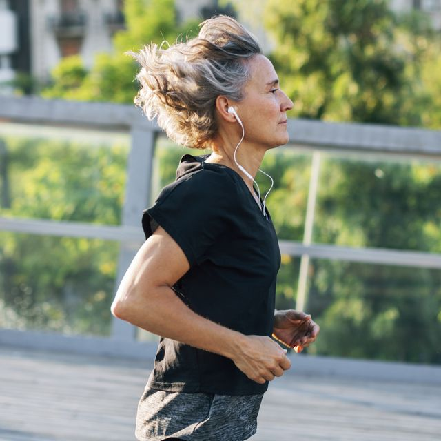 Side view of woman jogging while listening music at bridge