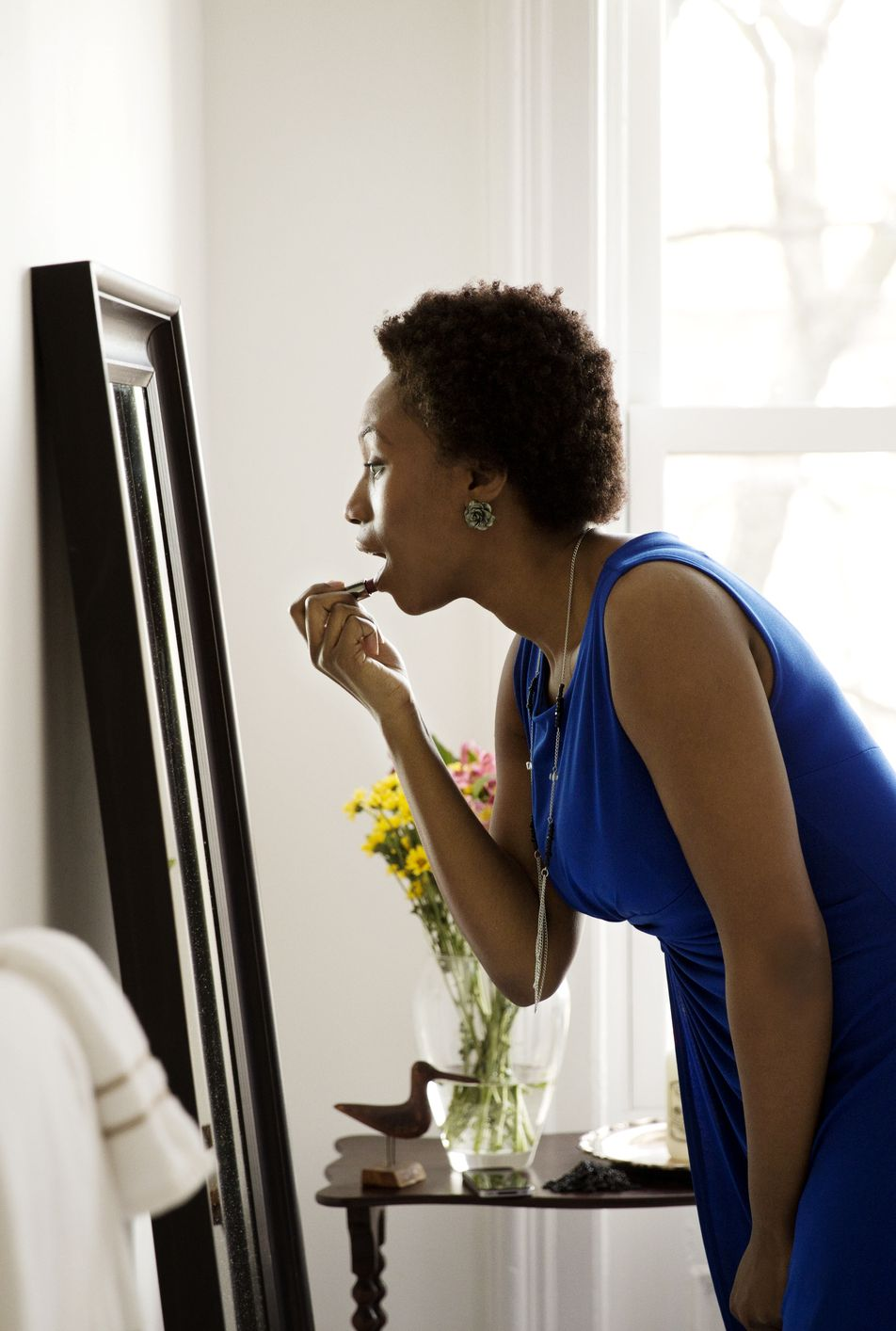 Side view of woman looking at mirror and applying lipstick