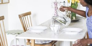 Side view of woman pouring water into glass from jug at dining table