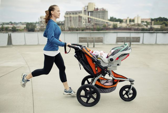 side view of woman pushing baby stroller while jogging in city