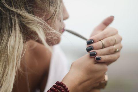 Vue latérale d'une femme fumant un joint de marijuana
