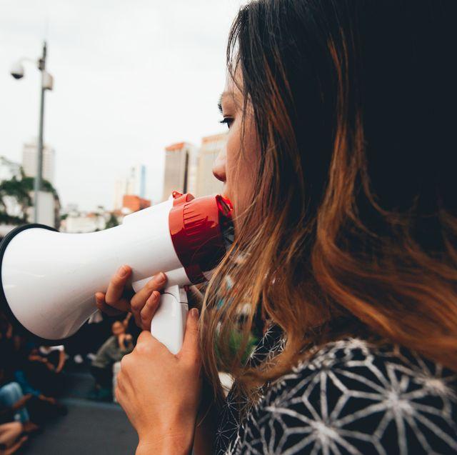 side view of woman talking on megaphone on city street