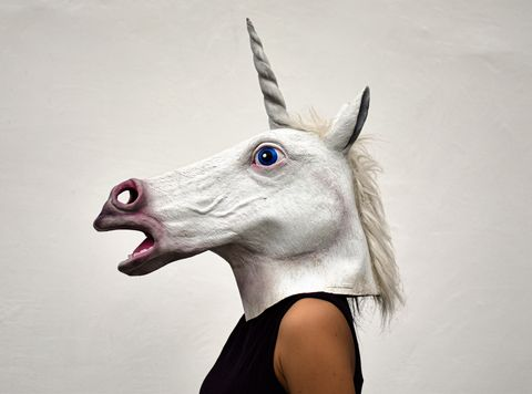 side view of woman wearing horse mask against white background