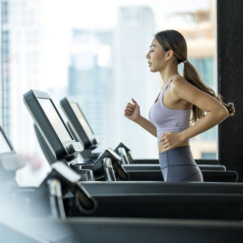 side view of young asian women athlete running or jogging on treadmill in a hotel sport club