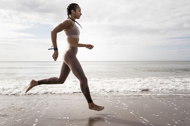 side view of young female runner running barefoot along waters edge at beach
