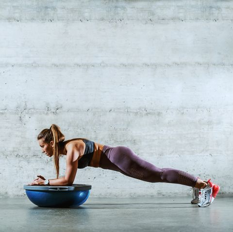 Side view of young muscular caucasian sporty brunette in sportswear with ponytail doing planks and leaning on bosu ball. Healthy lifestyle concept.
