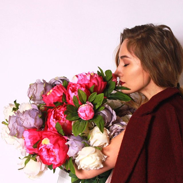 side view of young woman smelling bouquet against white background
