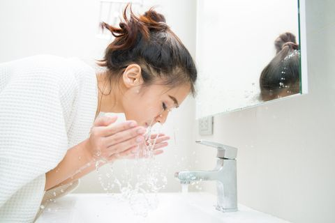 side view of young woman washing face in bathroom at home