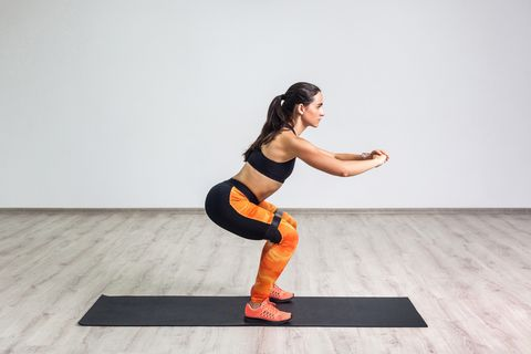 side view portrait of young sporty healthy beautiful woman in black top and orange leggings doing squatting with elastic resistance band