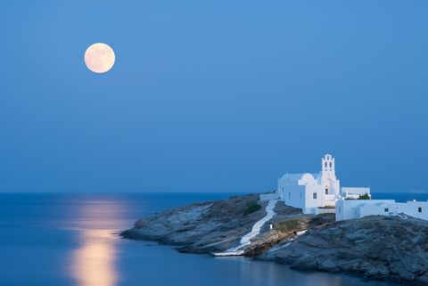 a summer picture of the island sifnos with the full moon and its reflections on the aegean sea the famous church of panagia chrysopigi on the foreground
