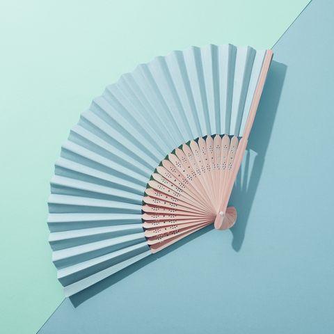 Hand fan on blue surface.