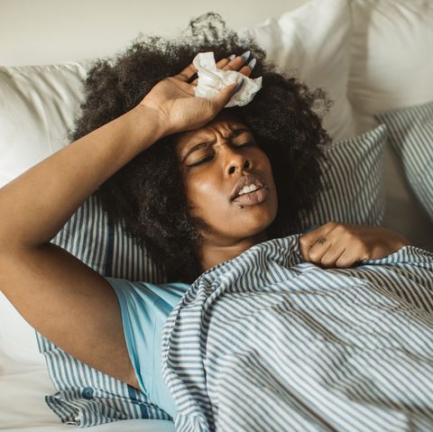 young african american woman feeling sick at home lying in bed, drinking tea and medicine daytime