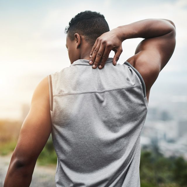 rearview shot of a sporty young man touching his neck while exercising outdoors