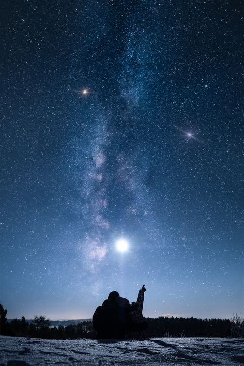 silhouette couple sitting on mountain against star field at night