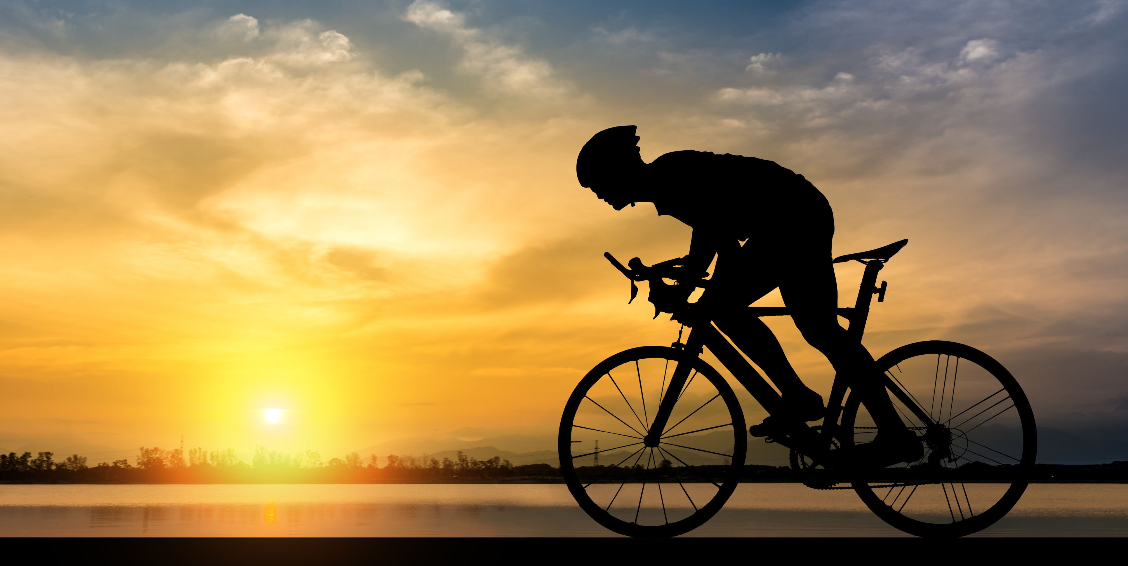 Silhouette Man Riding Bicycle Against Sky During Sunset