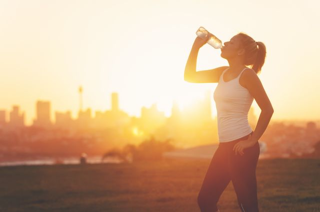 silhouette of a woman drinking form a cold water bottle