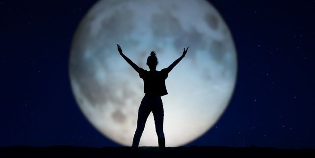 silhouette of a woman standing in the night with the arms up, giant moon in the background