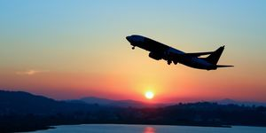 Silhouette of an airplane just after take off during sunset