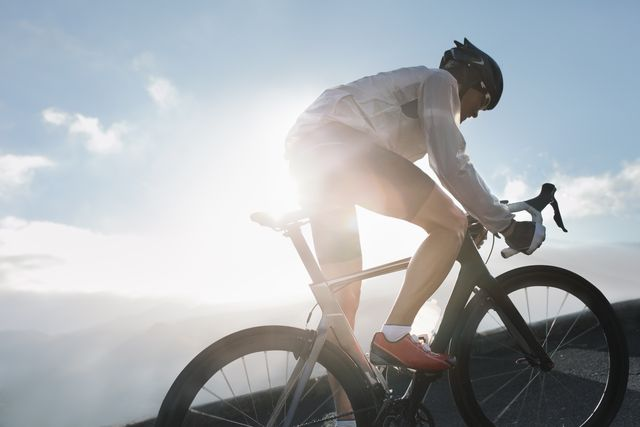 silhouette of cyclist riding up in high mountains at sunrise