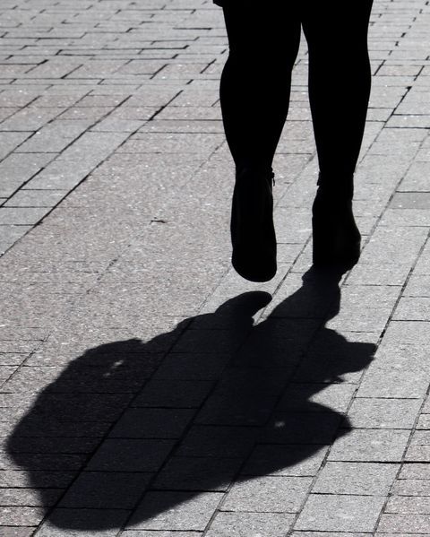 Silhouette of fat woman walking down the street, black shadow on pavement