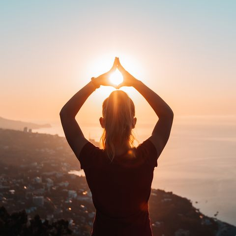 silhouette of woman doing yoga at sunrise