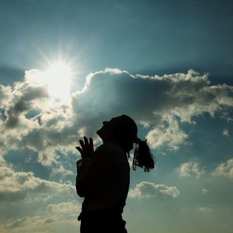 silhouette of woman praying at sunset