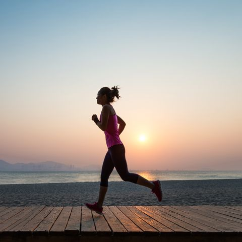 silhouette of young woman jogging on shore at sunrise