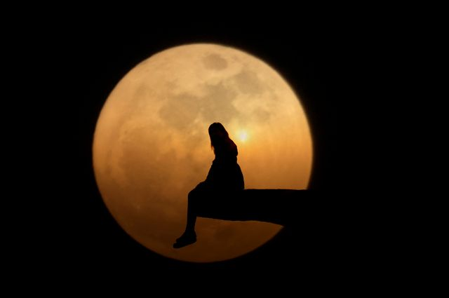 silhouette woman sitting on cliff against moon at night