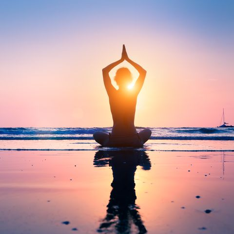 Silhouette young woman practicing yoga lotus position, meditating, beach