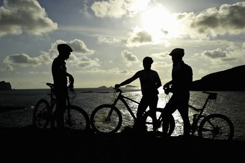 tres hombres hacen un descanso en su ruta de bicicleta de montaña al atardecer de ibiza
