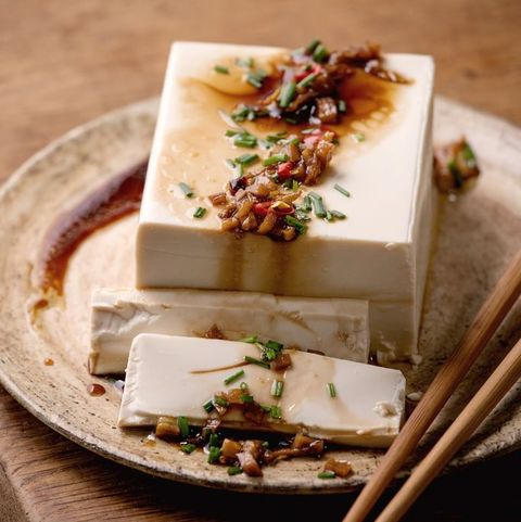 silk tofu japanese soy cheese whole piece with chili chive ginger and soy sauce topping on ceramic plate with chopsticks over wooden table