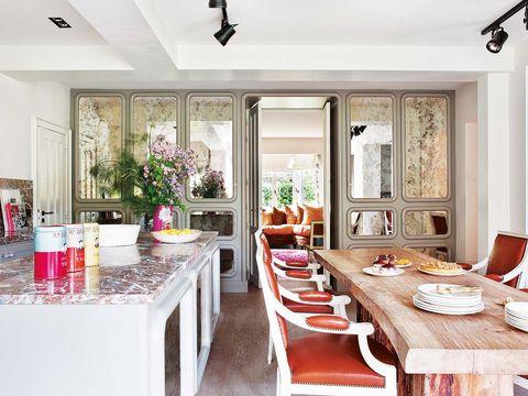 cocina con comedor con mesa de madera en bruto y sillas estilo luis xvi