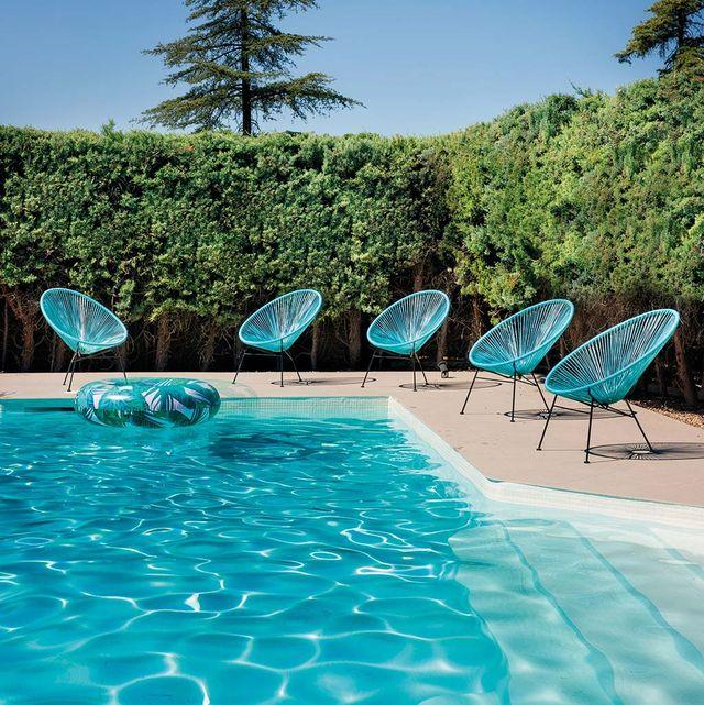 sillas acapulco de color azul en la piscina