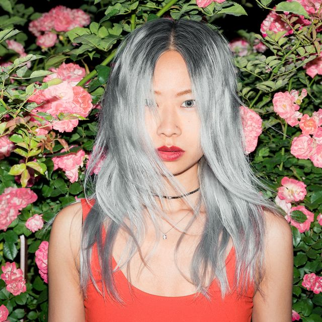 woman with dyed silver hair in front of flowers