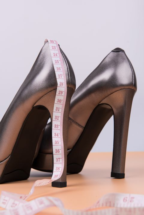 Silver high heel women shoes and measuring tape on yellow