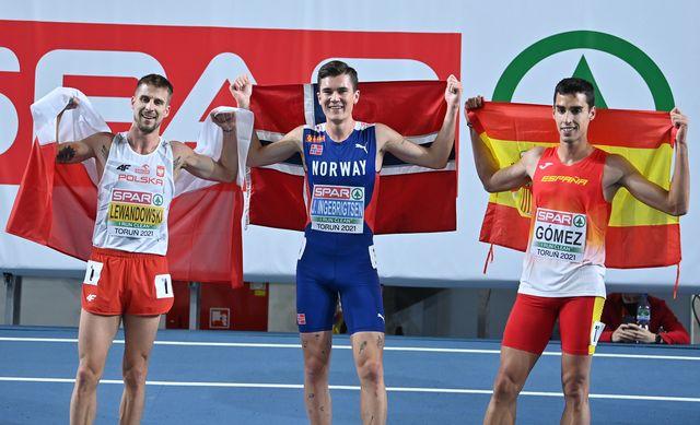 jesús gómez posa con la bandera de españa tras su medalla de plata en los 1500 metros de torun 2021