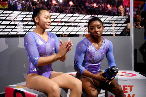 simone biles and sunisa lee sitting side by side in purple and silver leotards during a competition