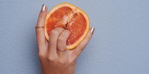 Vrouwen vingers in een sinaasappel