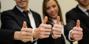 Midsection Of Business People Showing Thumbs Up While Standing In Office