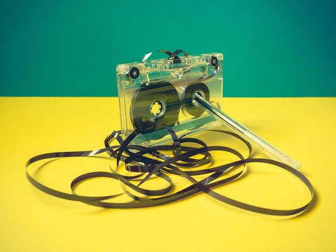 Single audio cassette tape with loose tape spilling from top cassette and a pen on vintage style