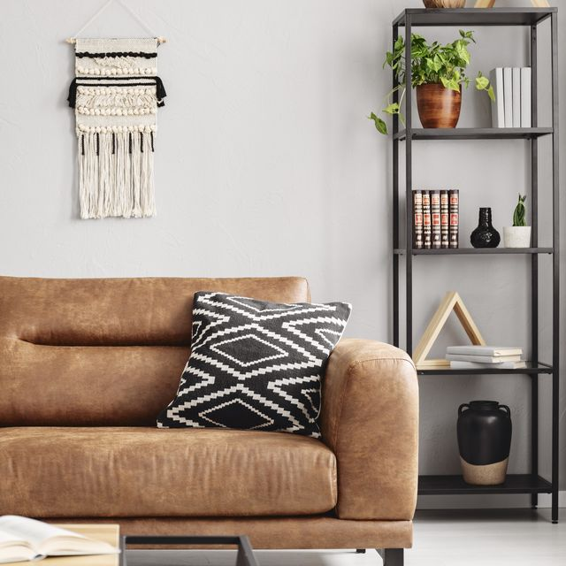 real photo of handmade macrame and mockup poster hanging on the wall in bright sitting room interior with leather sofa and metal rack with decor and books