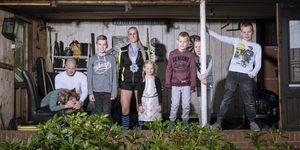 zes kinderen met vader en moeder in schuur met hond