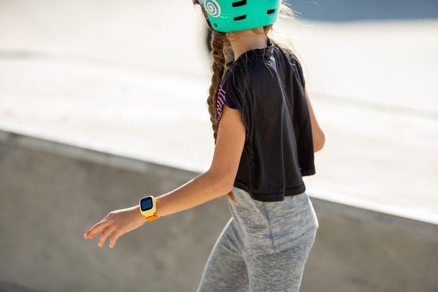 skateboarding girl wearing smart watch while riding