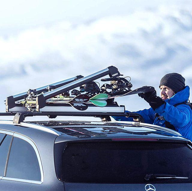 man adjusting snowboard on car roof rack