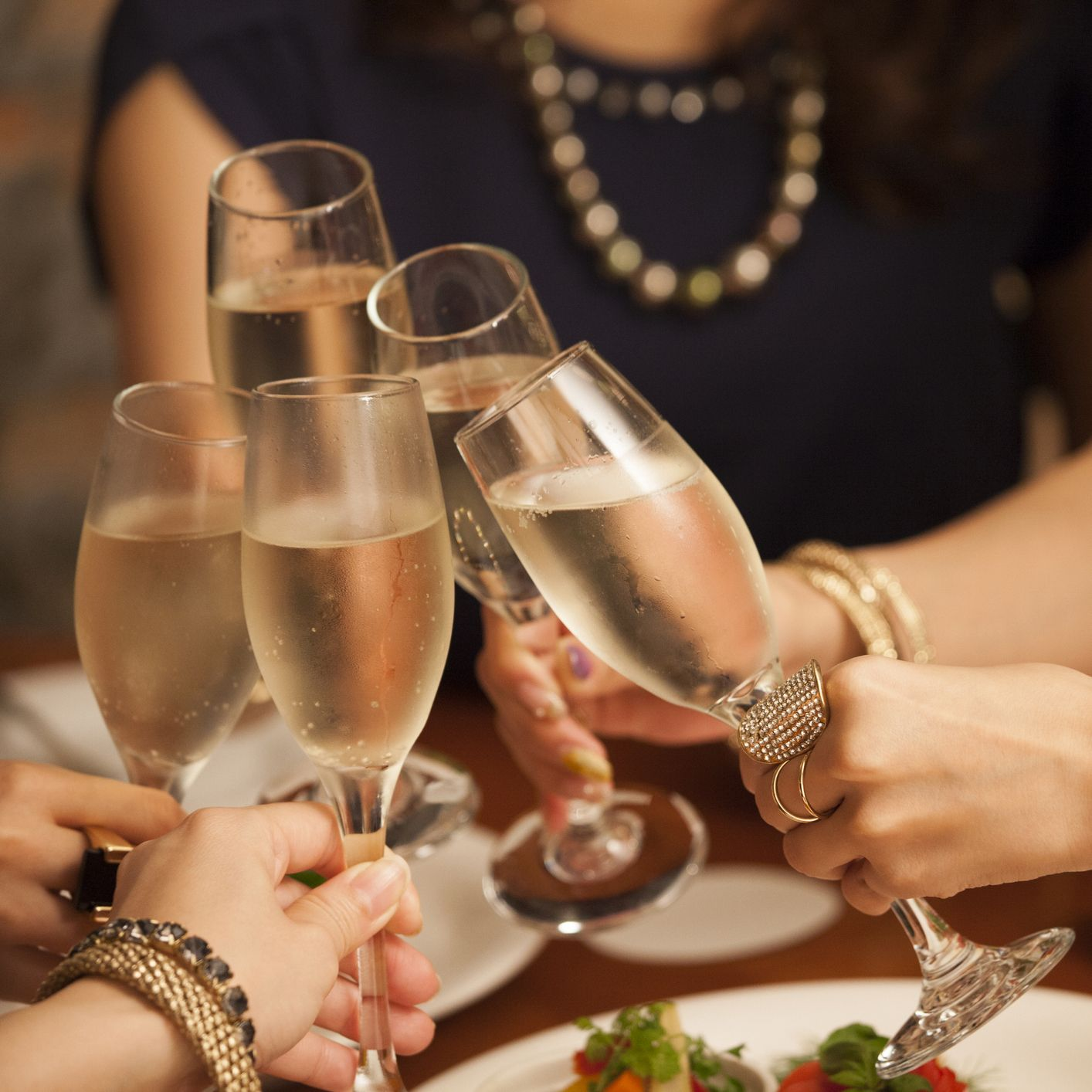 Close-up of the hands of the girls making a toast.