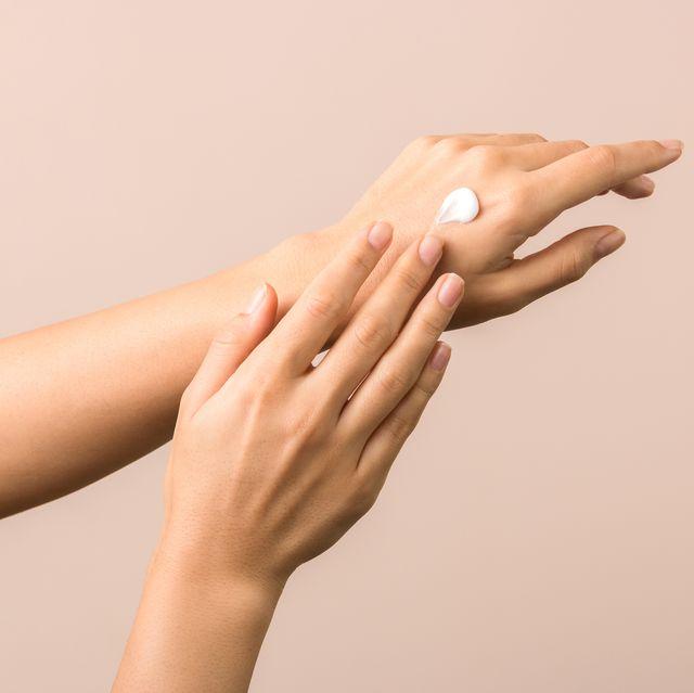 skincare close up view of woman hand moisturising them with cream skincare