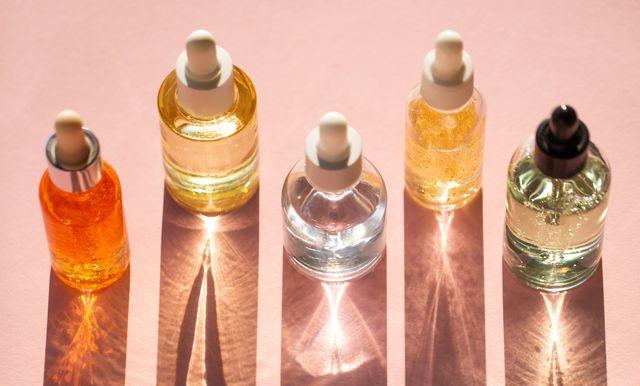 vijf flesjes met skincare producten op een rij gefotografeerd van bovenaf op een roze achtergrond