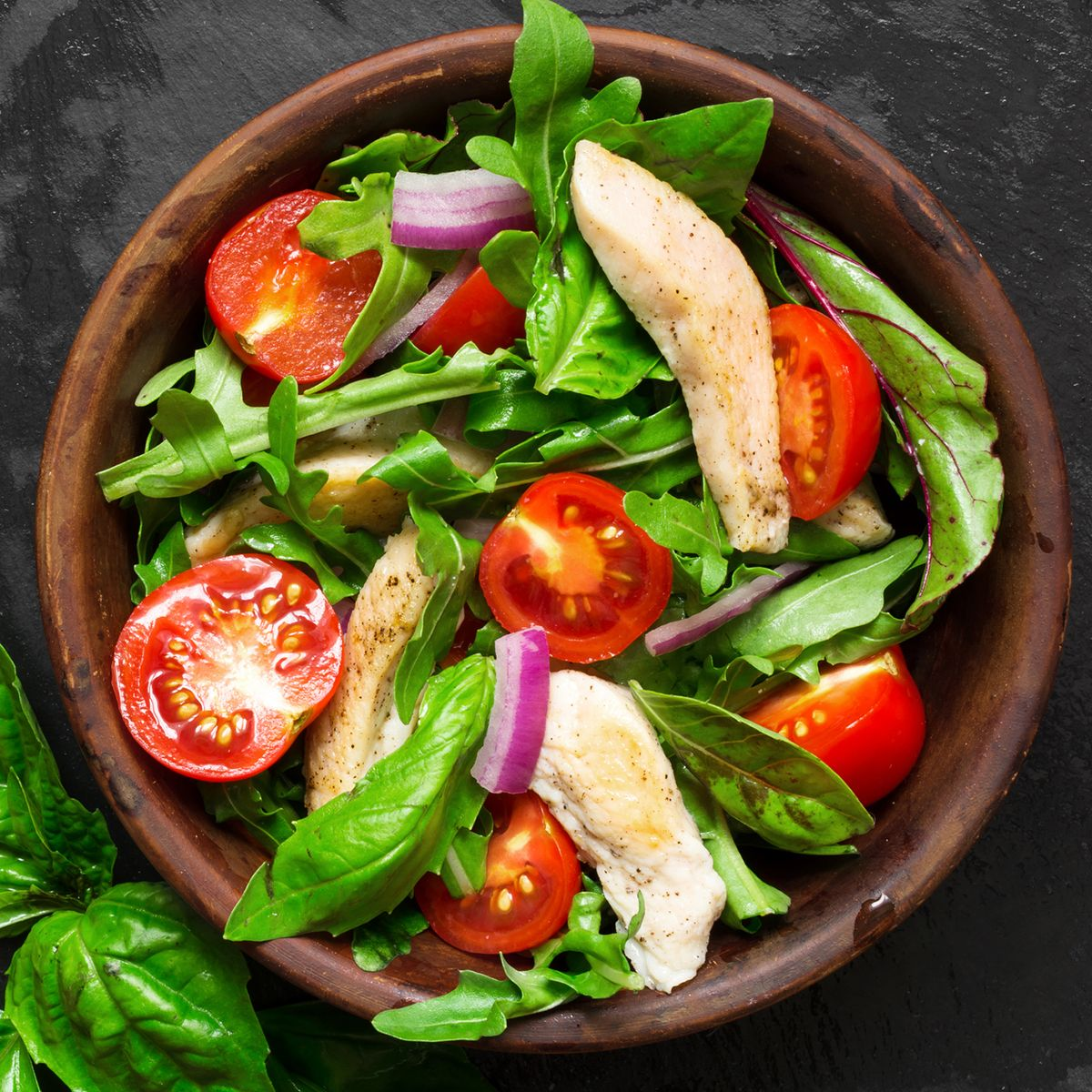 Fresh salad with chicken breast, arugula, basil and tomato over dark stone background